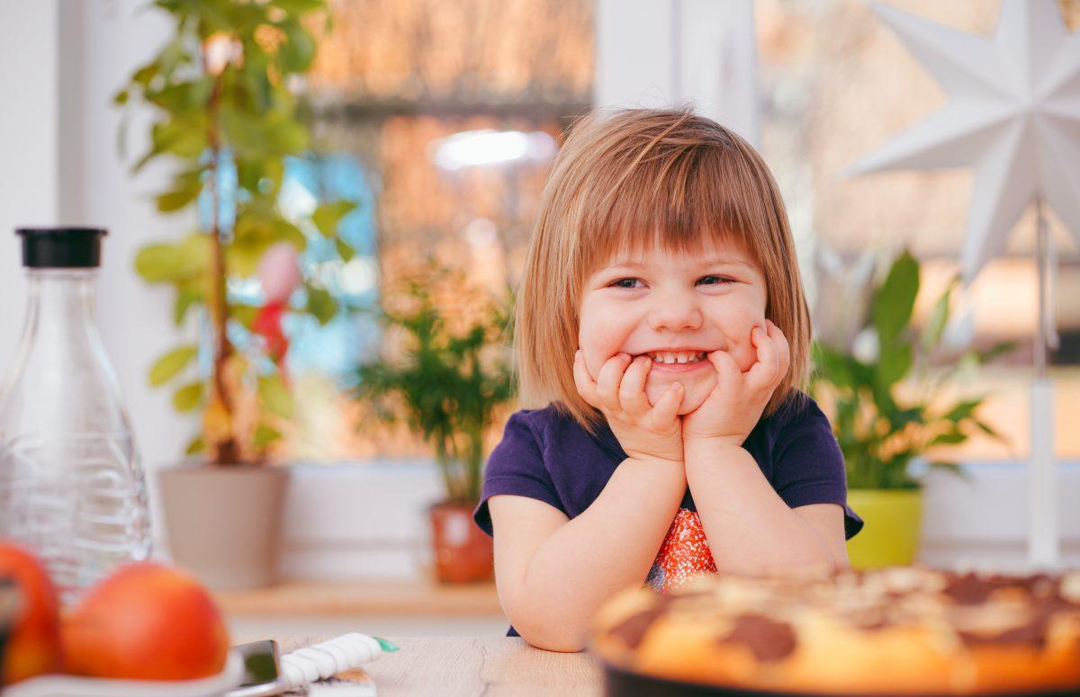 lite barn smiler ved middagsbordet